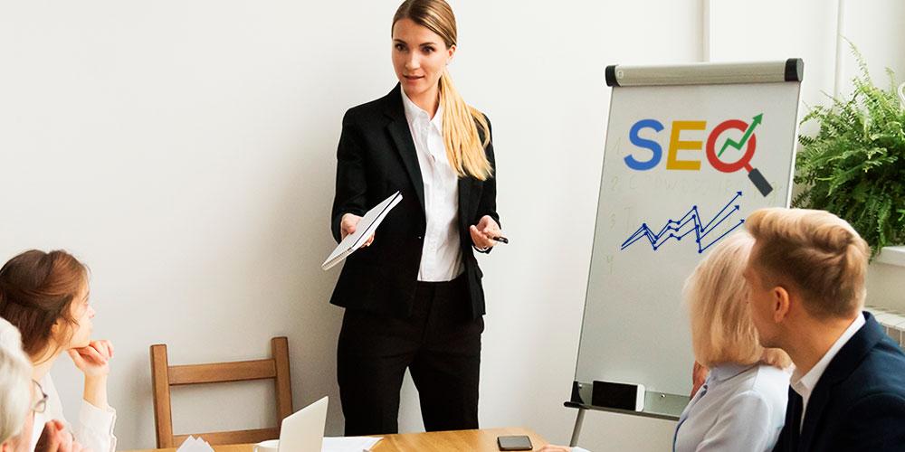 Mulher executiva vestida com roupa social realiza uma palestra para um grupo de executivos sobre como funciona o SEO. No cavalete utilizado por ela na apresentação, podemos ler a palavra SEO escrita com as mesmas cores do Google.